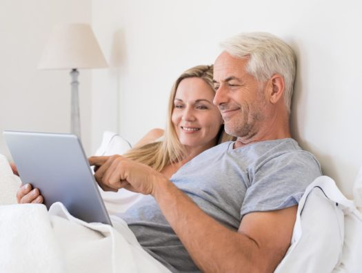 A happy couple in bed, who got the ED treatment in Oakwood Health Network Clinic