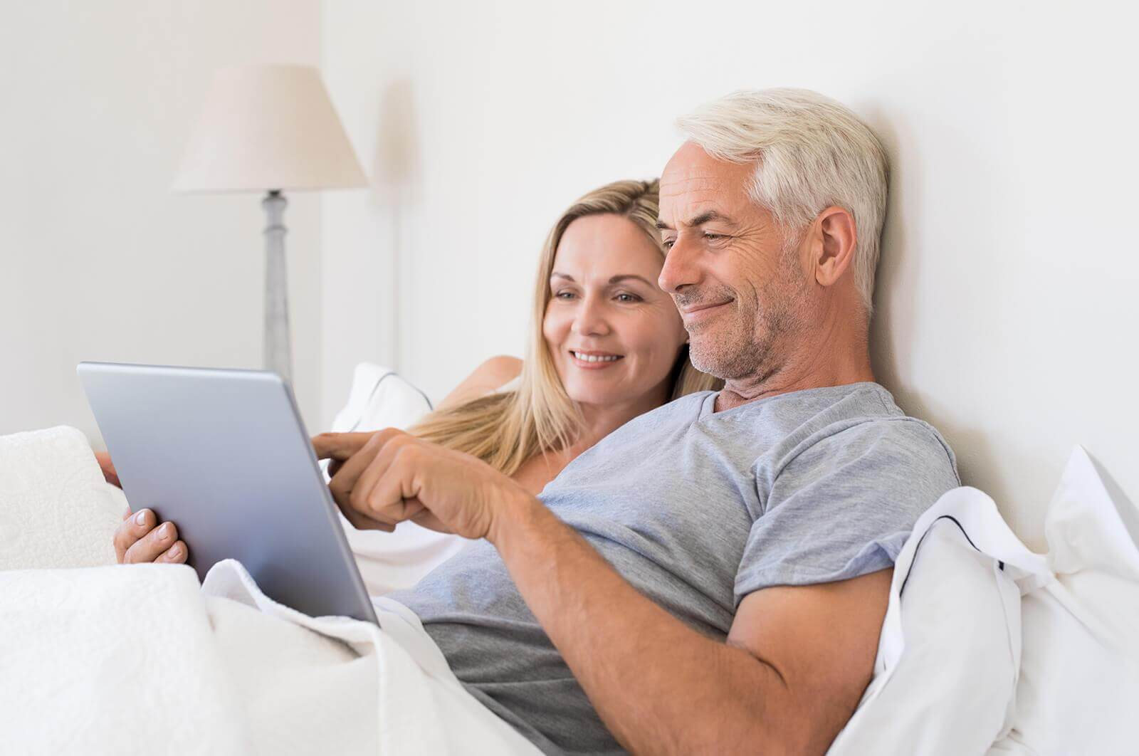 couple in bed with tablet